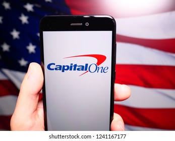 Murcia, Spain; Nov 21, 2018: Capital One logo in phone with United States flag on background. Capital One Financial Corporation is a bank holding company