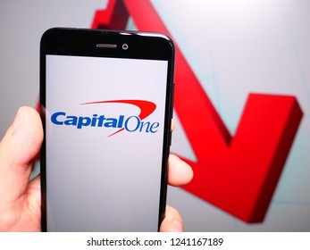 Murcia, Spain; Nov 21, 2018: Capital One logo in phone with losses graphic on background. First person view