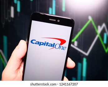 Murcia, Spain; Nov 21, 2018: Hand holding phone with Capital One logo displayed in it with fluctuating graphic on background. First person view