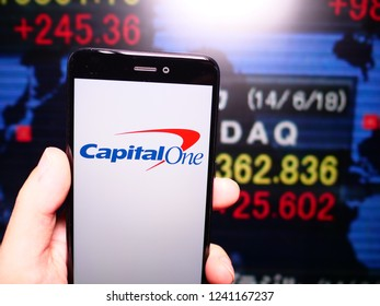 Murcia, Spain; Nov 21, 2018: Capital One logo in phone with New York stock exchange (NYSE) screen on background. First person view