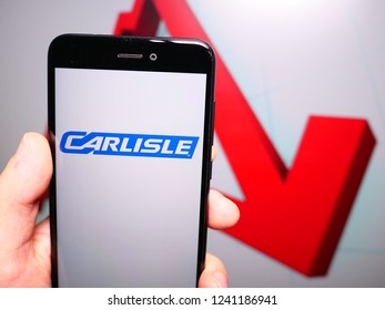 Murcia, Spain; Nov 21, 2018: Carlisle Companies logo in phone with losses graphic on background. First person view