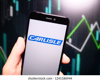 Murcia, Spain; Nov 21, 2018: Hand holding phone with Carlisle Companies logo displayed in it with fluctuating graphic on background. First person view