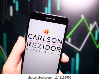 Murcia, Spain; Nov 21, 2018: Hand holding phone with Carlson Rezidor Hotel Group logo displayed in it with fluctuating graphic on background. First person view