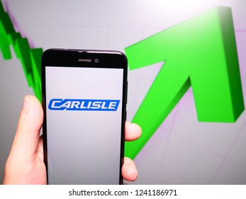Murcia, Spain; Nov 21, 2018: Carlisle Companies logo in phone with rises graphic on background. First person view