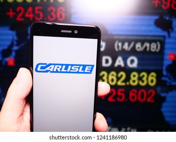 Murcia, Spain; Nov 21, 2018: Carlisle Companies logo in phone with New York stock exchange (NYSE) screen on background. First person view