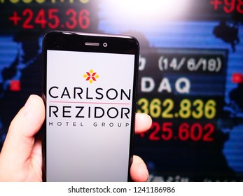 Murcia, Spain; Nov 21, 2018: Carlson Rezidor logo in phone with stock exchange screen on background. First person view