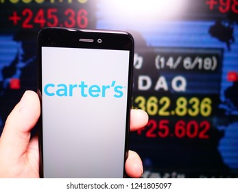 Murcia, Spain; Nov 21, 2018: Carter's logo in phone with New York stock exchange (NYSE) screen on background. First person view