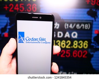 Murcia, Spain, Nov 21, 2018: Cedar Fair logo in phone with New York stock exchange (NYSE) screen on background. First person view