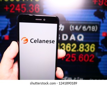 Murcia, Spain; Nov 21, 2018: Celanese Corporation logo in phone with New York stock exchnage (NYSE) screen on background. First person view