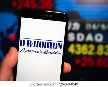 Murcia, Spain; Nov 27, 2018: D. R. Horton logo in phone with New York stock exchange (NYSE) screen on background. First person view