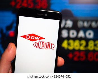 Murcia, Spain; Nov 27, 2018: DowDuPont logo in phone with New York stock exchange (NYSE) screen on background. First person view