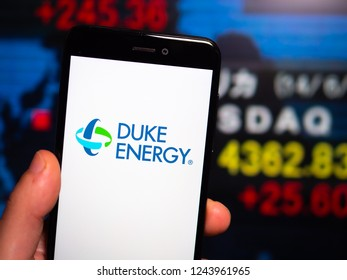 Murcia, Spain; Nov 27, 2018: Duke Energy logo in phone with New York stock exchange (NYSE) screen on background. First person view