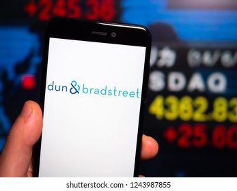 Murcia, Spain; Nov 27, 2018: Dun & Bradstreet logo in phone with New York stock exchange (NYSE) screen on background. First person view