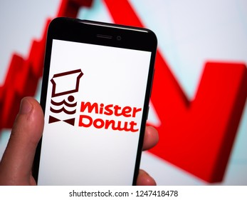 Murcia, Spain; Nov 27, 2018: Mister Donut logo in phone with losses graphic on background. First person view