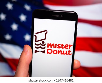 Murcia, Spain; Nov 27, 2018: Mister Donut logo in phone with United States flag on background. Mister Donut is a fast food franchise