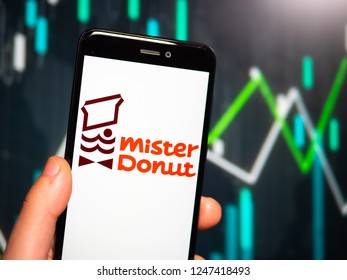 Murcia, Spain; Nov 27, 2018: Hand holding phone with Mister Donut logo displayed in it with fluctuating graphic on background. First person view