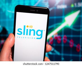 Murcia, Spain; Nov 27, 2018: Sling TV logo in phone with earnings graphic on background. Sling Television is an American over-the-top internet television service