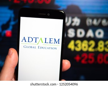Murcia, Spain; Nov 27, 2018: Adtalem Global Education logo in phone with New York stock exchange (NYSE) screen on background. First person view