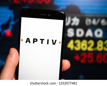 Murcia, Spain; Nov 27, 2018: Aptiv PLC logo in phone with New York stock exchange (NYSE) screen on background. First person view