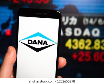 Murcia, Spain; Nov 27, 2018: Dana Incorporated logo in phone with New York stock exchange (NYSE) screen on background. First person view