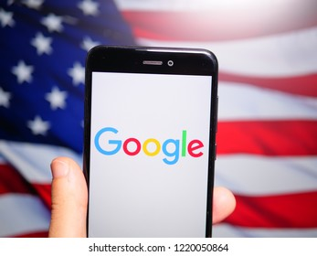 Murcia, Spain; Nov 3, 2018: Google LLC logo in phone with United States flag on background. Google LLC is an American multinational technology company that specializes in Internet