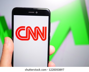Murcia, Spain; Nov 3, 2018: CNN red logo in phone with rises graphic on background. First person view