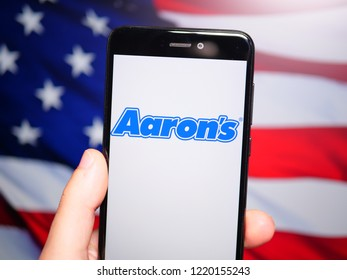 Murcia, Spain; Nov 3, 2018: Aaron's blue logo in phone with United States flag on background. Aaron's, Inc. is a lease-to-own retailer