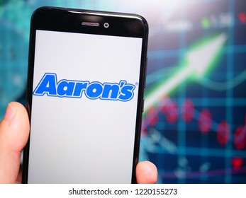 Murcia, Spain; Nov 3, 2018: Aaron's blue logo in phone with earnings graphic on background. Aaron's, Inc. is a lease-to-own retailer