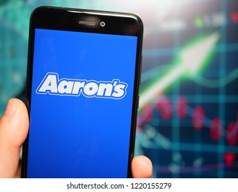 Murcia, Spain; Nov 3, 2018: Aaron's white logo in phone with earnings graphic on background. Aaron's, Inc. is a lease-to-own retailer