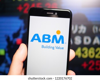 Murcia, Spain; Nov 3, 2018: ABM Industries logo in phone with New York stock exchange (NYSE) screen on background. First person view