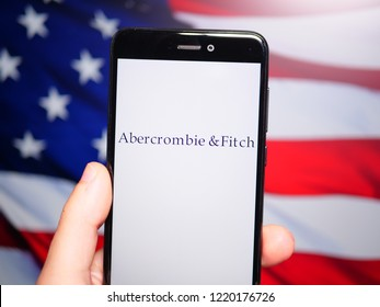 Murcia, Spain; Nov 3, 2018: Abercrombie & Fitch logo in phone with United States flag on background. is an American retailer that focuses on upscale casual wear