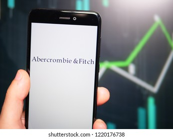 Murcia, Spain; Nov 3, 2018: Hand holding phone with Abercrombie & Fitch logo displayed in it with fluctuating graphic on background. First person view