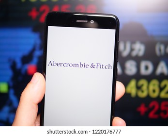 Murcia, Spain; Nov 3, 2018: Abercrombie & Fitch logo in phone with New York stock exchange (NYSE) screen on background. First person view
