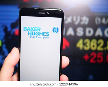 Murcia, Spain; Nov 6, 2018: Baker Hughes (BHGE) logo in phone with New York stock exchange (NYSE) screen on background. First person view