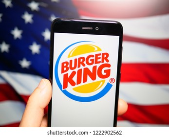 Murcia, Spain; Nov 6, 2018: Burger King logo in phone with United States flag on background. Burger King (BK) is an American global chain of hamburger fast food restaurants