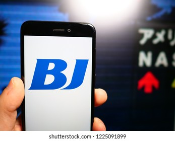 Murcia, Spain; Nov 7, 2018: BJ Services Company logo in phone with stock exchange screen on background. First person view
