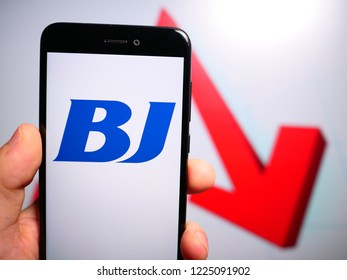 Murcia, Spain; Nov 7, 2018: BJ Services Company logo in phone with losses graphic on background. First person view