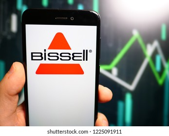Murcia, Spain; Nov 7, 2018: Hand holding phone with Bissell Homecare logo displayed in it with fluctuating graphic on background. First person view
