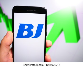 Murcia, Spain; Nov 7, 2018: BJ Services Company logo in phone with rises graphic on background. First person view