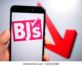 Murcia, Spain; Nov 7, 2018: BJ's Wholesale Club logo in phone with losses graphic on background. First person view