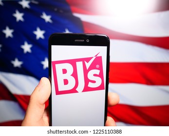 Murcia, Spain; Nov 7, 2018: BJ's Wholesale Club logo in phone with United States flag on background. BJ's Wholesale Club is an American membership-only warehouse club chain