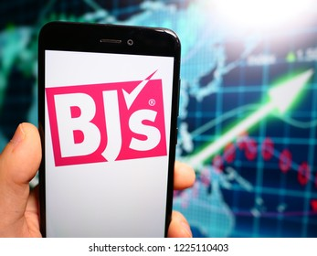 Murcia, Spain; Nov 7, 2018: BJ's Wholesale Club logo in phone with earnings graphic on background. BJ's Wholesale Club is an American membership-only warehouse club chain