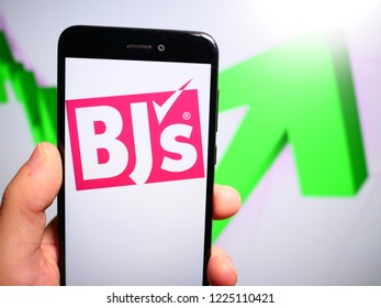 Murcia, Spain; Nov 7, 2018: BJ's Wholesale Club logo in phone with rises graphic on background. First person view