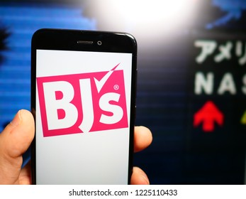 Murcia, Spain; Nov 7, 2018: BJ's Wholesale Club logo in phone with New York stock exchange (NYSE) screen on background. First person view