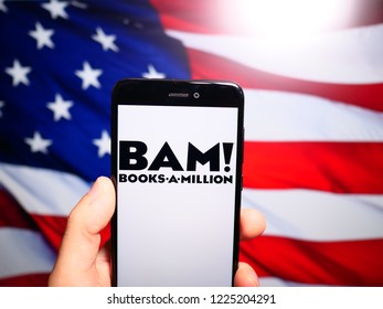 Murcia, Spain; Nov 7, 2018: Books A Million (BAM!) black logo in phone with United States flag on background. Books a Million owns and operates the second largest bookstore chain in the United States