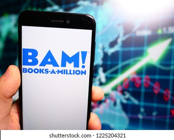 Murcia, Spain; Nov 7, 2018: Books a Million (BAM!) blue logo in phone with earnings graphic on background. Books-A-Million owns and operates the second largest bookstore chain in the United States