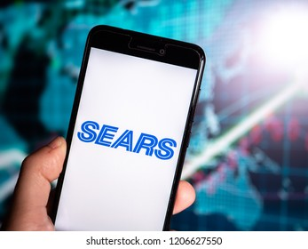 Murcia, Spain; Oct 16, 2018: Hand holding phone with Sears blue logo displayed int it with earnings graphic on background. Sears Holding Corporation crash