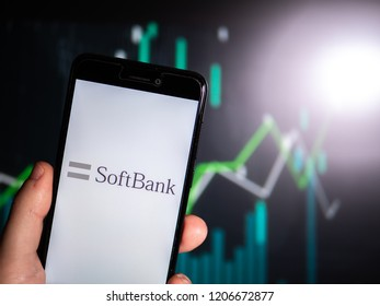 Murcia, Spain; Oct 16, 2018: Hand holding phone with SoftBank Group logo in it with fluctuating graphic on background. First person view