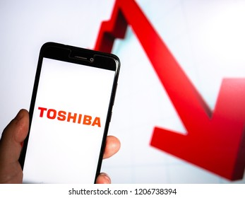Murcia, Spain; Oct 16, 2018: Toshiba Corporation logo in phone with losses graphic on background. First person view