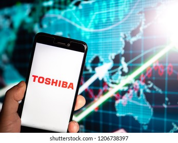 Murcia, Spain; Oct 16, 2018: Toshiba Corporation logo in phone with earnings graphic on background. First person view